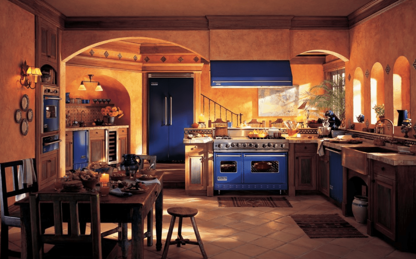 Southwestern kitchen accented with blue appliances and slate flooring. It includes wooden cabinetry and dining space.