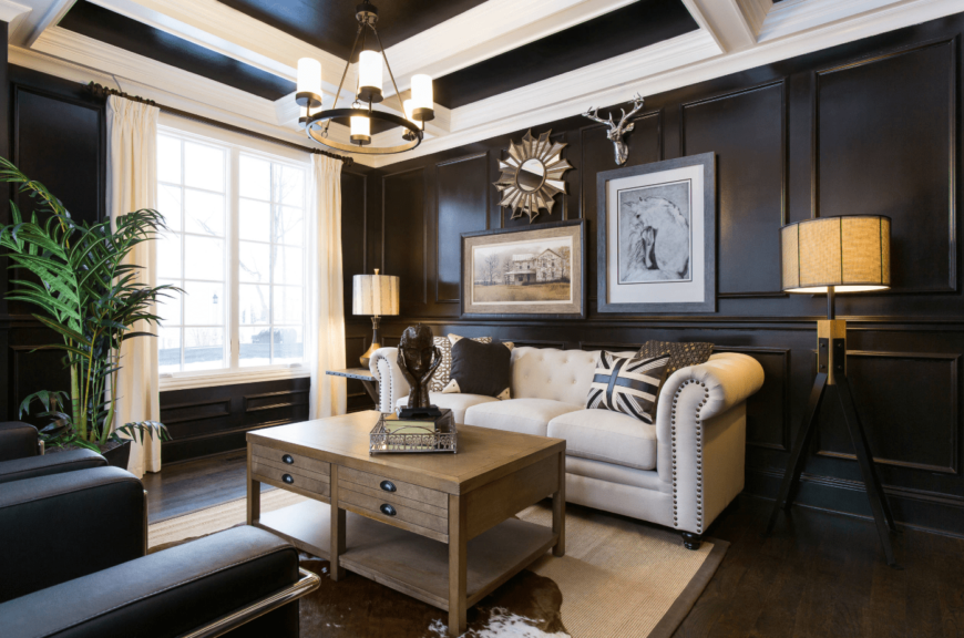 Traditional living room illuminated by a wrought iron chandelier that hung from the coffered ceiling. It is designed with a sunburst mirror along with framed arts and stag head decor mounted on the black wainscoted wall.