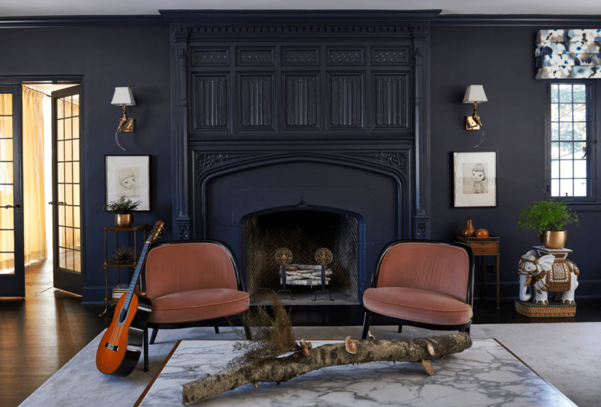 A pair of terracotta chairs sit in front of the ornate fireplace lighted by wall sconces above wall art pieces in this black living room.