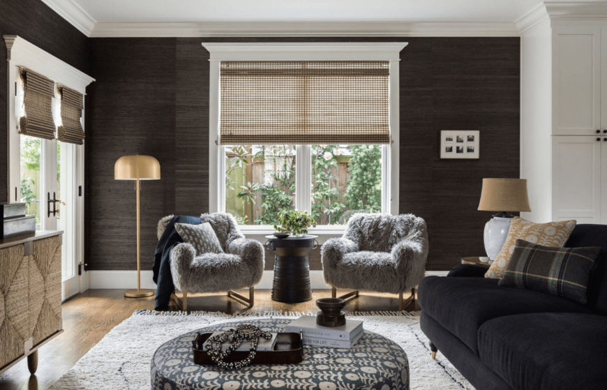 Airy living room features a pair of gray fur chairs beneath the glass window lighted by a brass floor lamp and paired with a round black table.