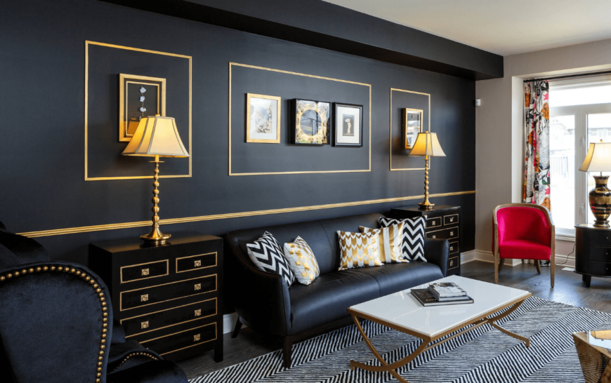 The gorgeous living room offers a black leather couch in between side tables topped with gold lamps. It has a black wall with gold lining and mounted frames.