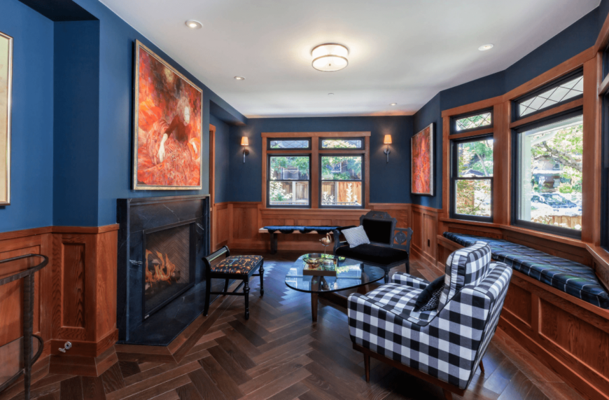 Gorgeous blue living room features a half dark wood wainscoting wall and herringbone patterned hardwood flooring. It has a built-in window seat nook fitted with a blue upholstered cushion and a contrasting black and white checkered chair.