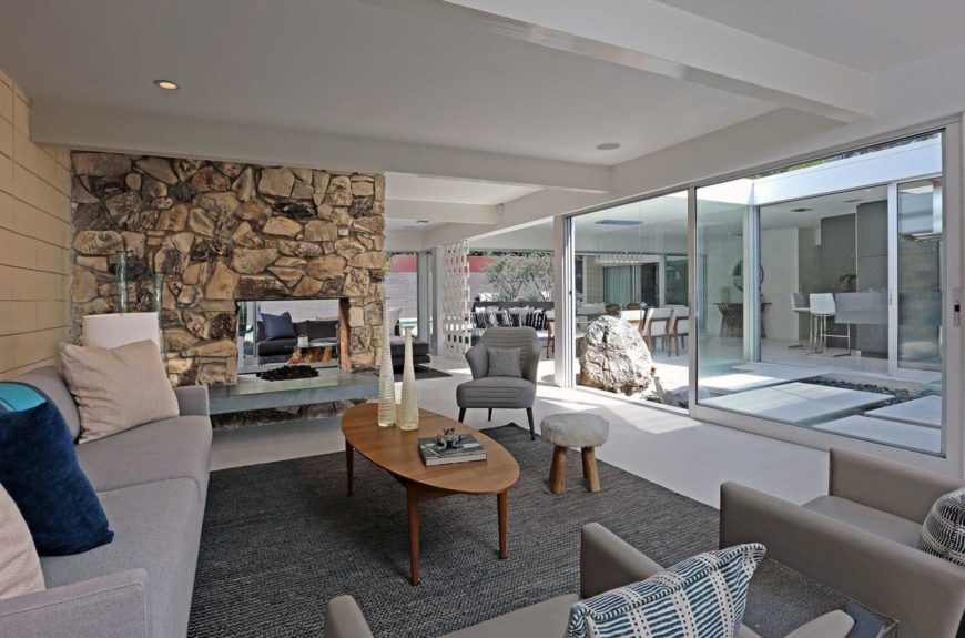The living room has glazed walls that bring outdoor views indoors as well as a stone fireplace and stylish furniture set with a neutral color scheme.