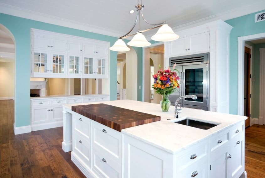 Spacious kitchen features a white kitchen island accented with a raised wood counter that complements with the hardwood flooring.