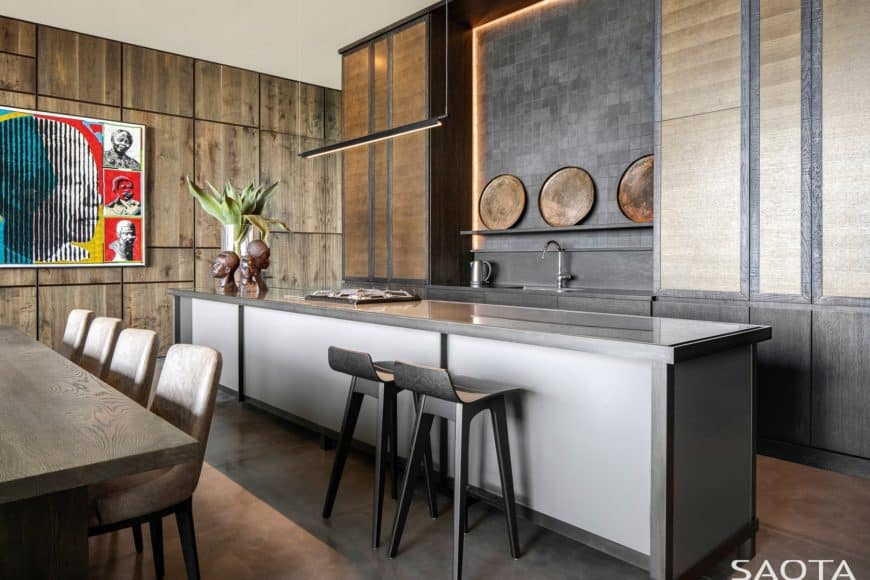 Contemporary kitchen showcases rustic wood paneled walls and dark island bar with a pair of black counter stools. You can sense a rich culture through the wall art piece and wooden decors.