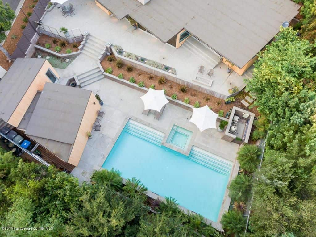 Aerial view of a vast patio with a pool, elegant stairways, and a backyard of tropical greenery.