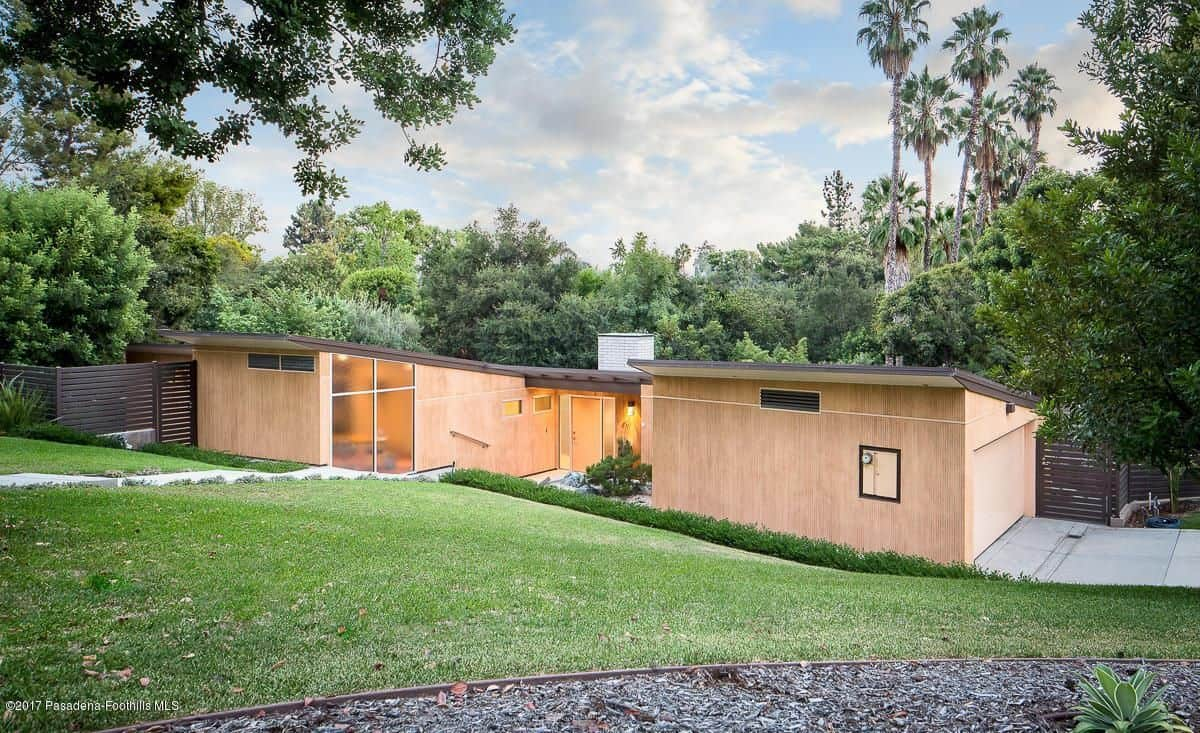 The wooden horizontal house on a sloping lot also features an expansive backyard of rolling grass.