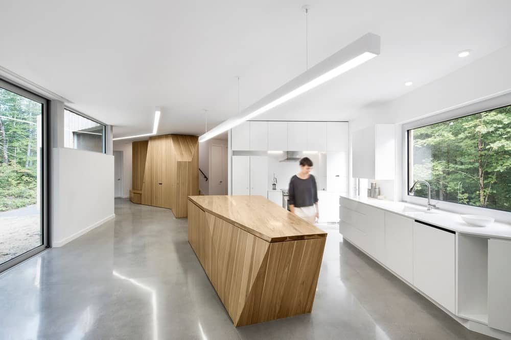 A sleek white kitchen lighted with a long modern pendant lamp that hung over a wooden breakfast island. It includes glazed window and door along with concrete flooring.