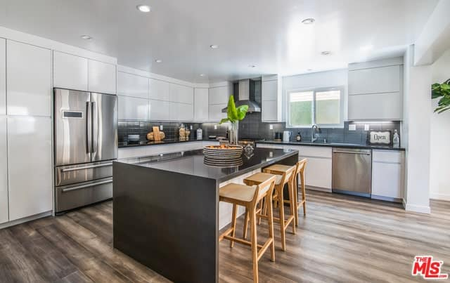 White contemporary kitchen features a dark wood breakfast island aligned with light wood counter stools over hardwood flooring. It has black subway tiles and recessed ceiling lights.
