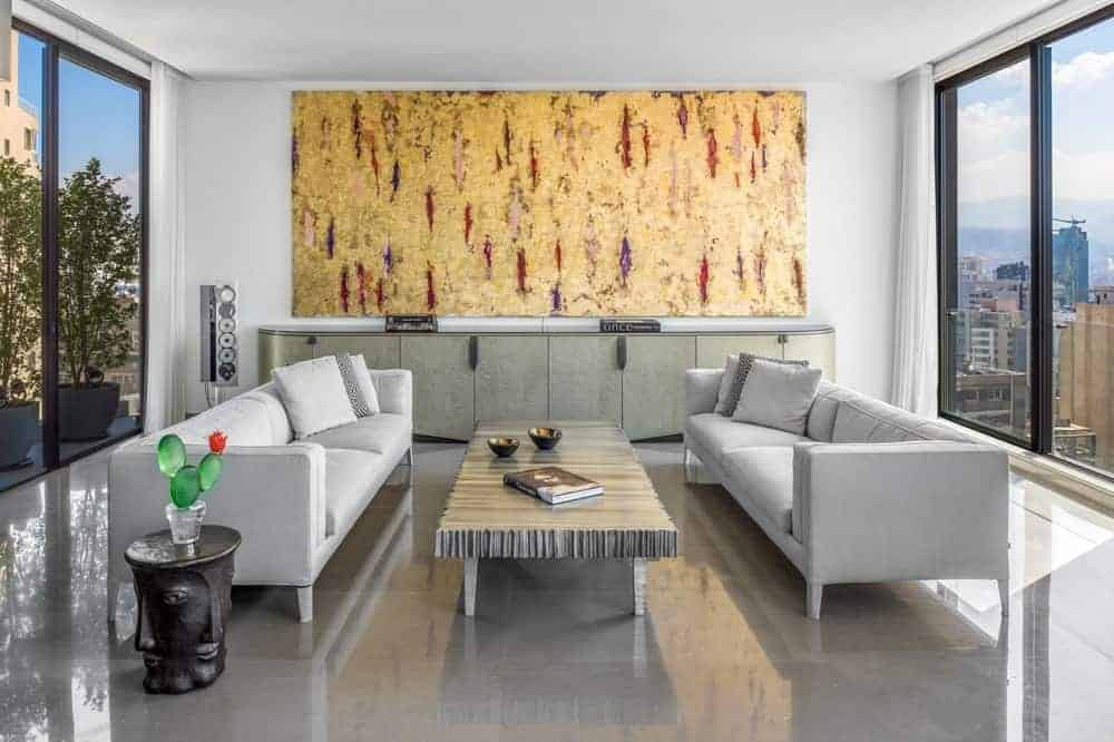 Gray sectional sofas flank a rectangular coffee table over high gloss tiled flooring. It faces the long console table that's accented by a large artwork on top.