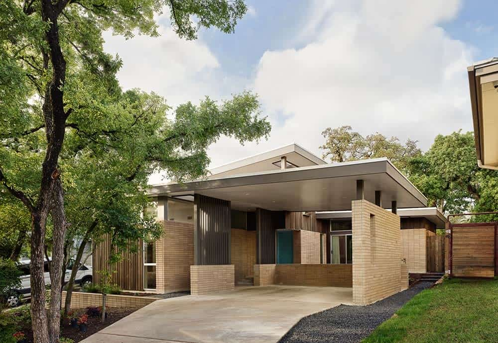 This is a close look at the front of the house with a large brick car port and a concrete driveway that matches the earthy tones of the house exteriors complemented by the landscaping.
