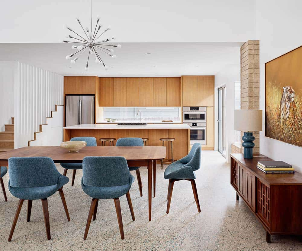 This is a close look at the dining area a few steps from the kitchen. It has a large wooden dining table surrounded by gray cushioned chairs and topped with a decorative lighting above hanging from the white ceiling.