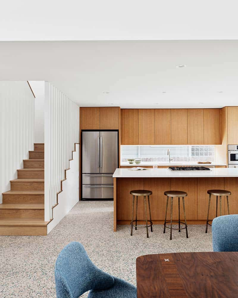 This is a simple kitchen only a few steps from the stairs and the dining area. It has a large wooden kitchen island that matches the tone of the wooden cabinetry on the far wall as well as the stools of the breakfast bar. These make the stainless steel appliances stand out.