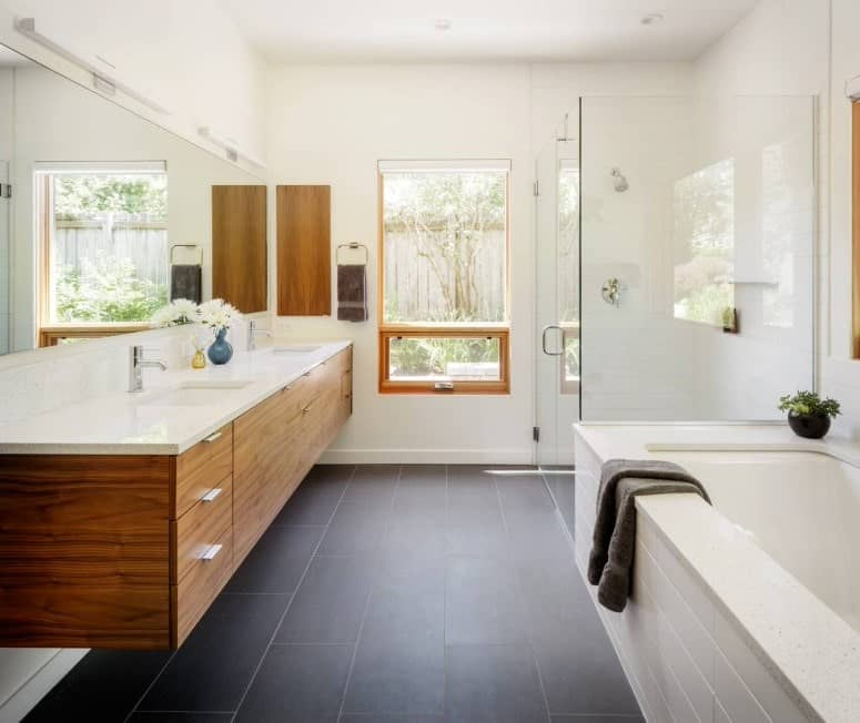 Primary bathroom with white walls and black tiles flooring. It offers a floating vanity double sink, a walk-in shower room and a deep soaking tub on the side.