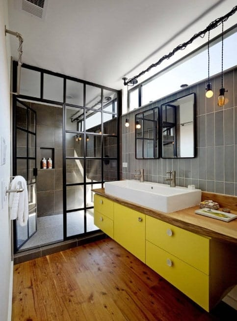 Primary bathroom featuring a stylish walk-in shower and a large vessel sink with two faucets. the room has hardwood flooring and gray tiles walls.