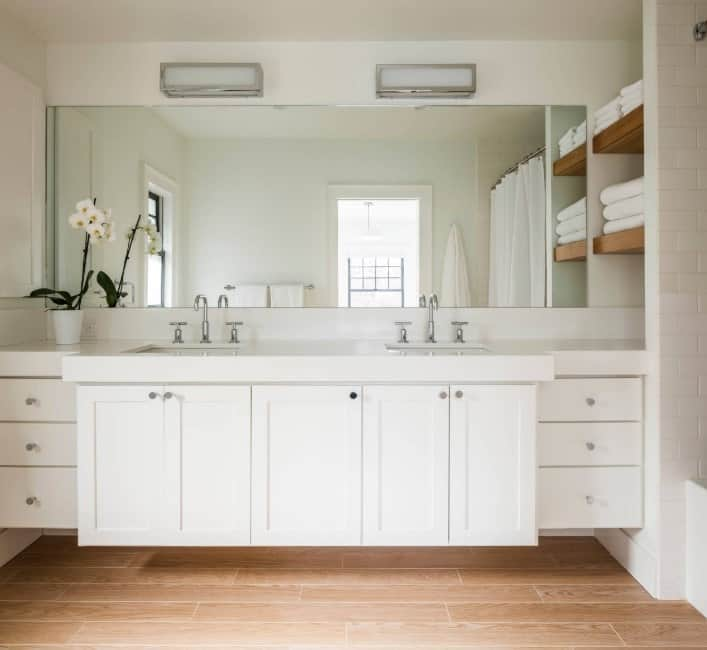 A focused shot at this primary bathroom's white floating vanity with two sinks. The room also has hardwood flooring.
