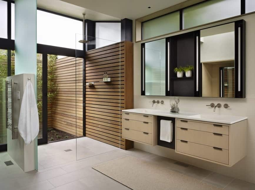 Modern primary bathroom with an open shower and a floating vanity with a double sink, along with tiles flooring.