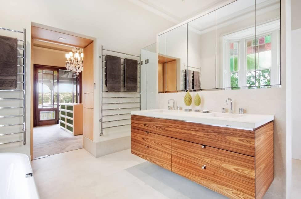 This primary bathroom offers a deep soaking tub and a double sink on a floating vanity. The room boasts white tiles flooring as well.
