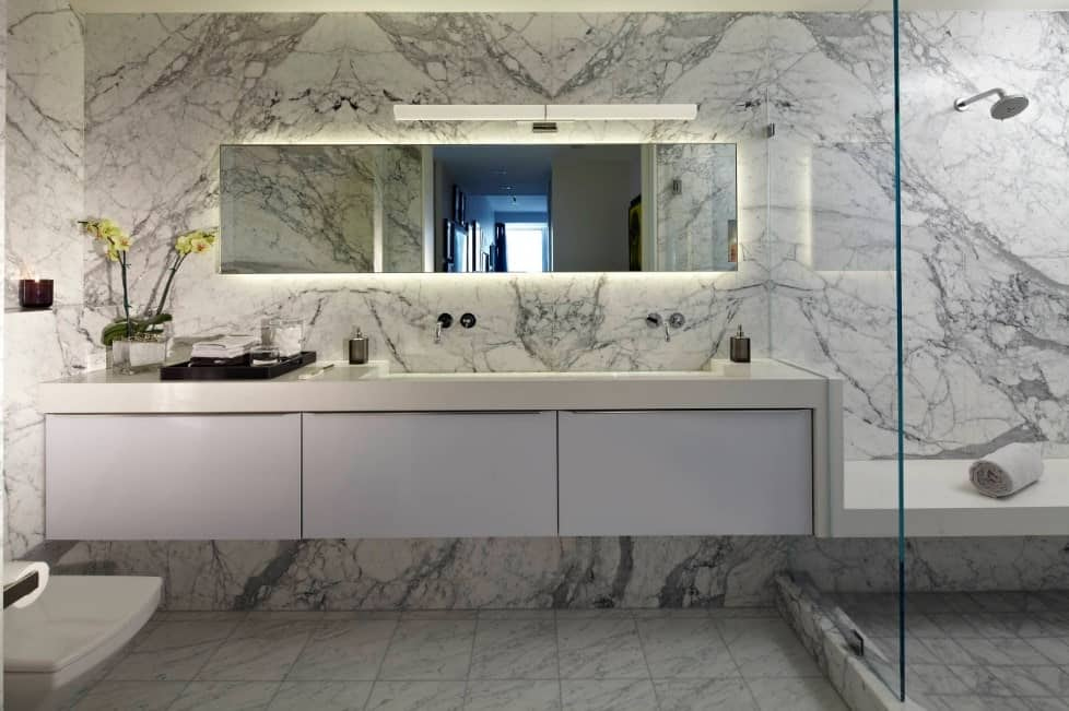 This primary bathroom boasts marvelous marble tiles walls and floors, along with a large floating vanity sink.