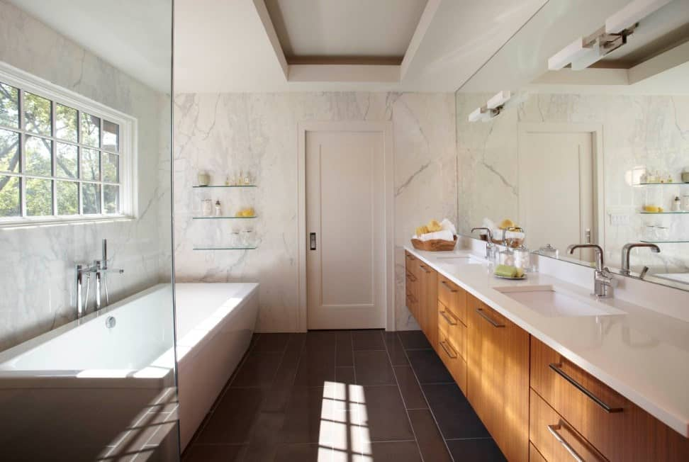Primary bathroom featuring white marble walls and a large white freestanding tub, along with a walk-in shower and a double sink.