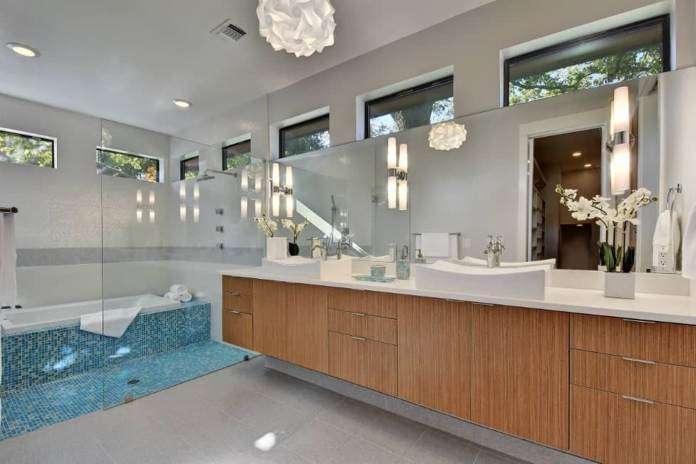 Large primary bathroom featuring an open shower and a drop-in tub set on the room's blue tiles flooring. The vessel sinks look classy as well.