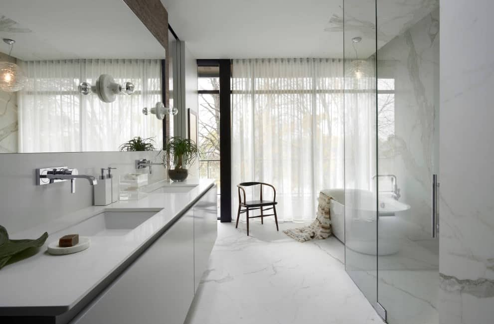 This primary bathroom offers a freestanding tub set on the room's marble flooring. There are two sinks and a walk-in shower with marble floors and walls.