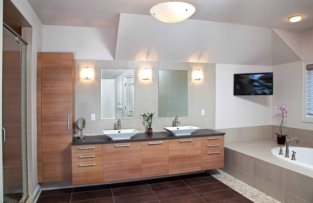 Large master bathroom featuring a couple of vessel sinks lighted by wall lights and a walk-in shower room along with a drop-in tub.