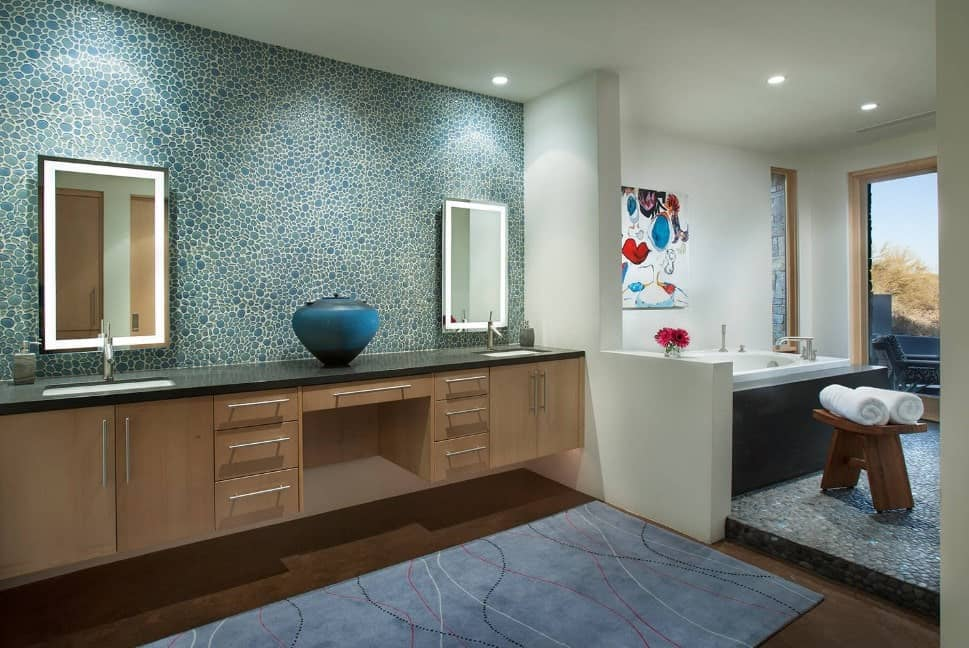 Primary bathroom with a stunning wall and a double sink, along with a small bathtub on the corner.