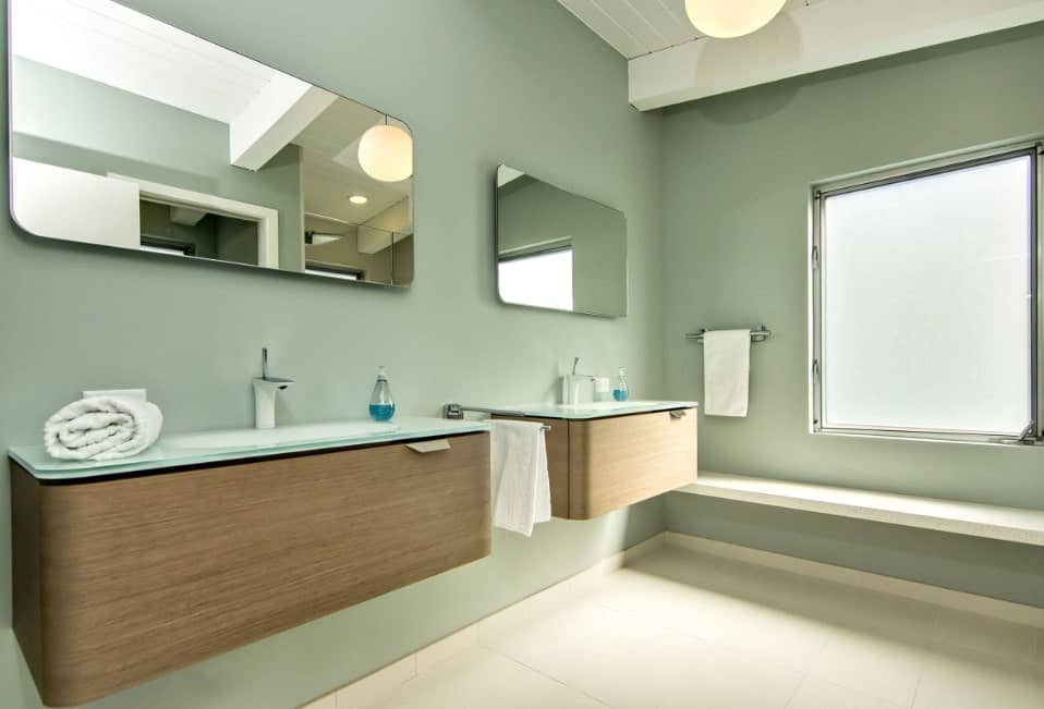 Primary bathroom featuring a bench seating near the windows and a couple of floating vanity sinks surrounded by green walls.