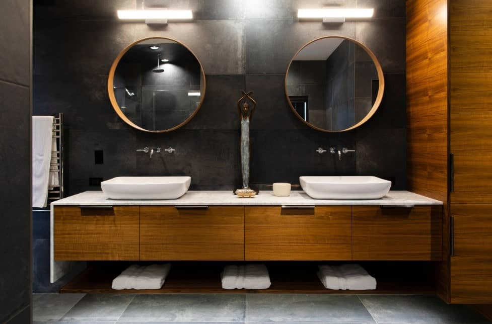 A master bathroom with elegant black walls and gray tiles flooring. It features a floating vanity with two vessel sinks lighted by wall lights.