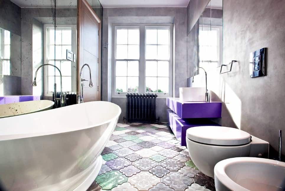 This primary bathroom offers very stylish flooring and handsome gray walls, along with an attractive violet floating vanity and a large freestanding tub.