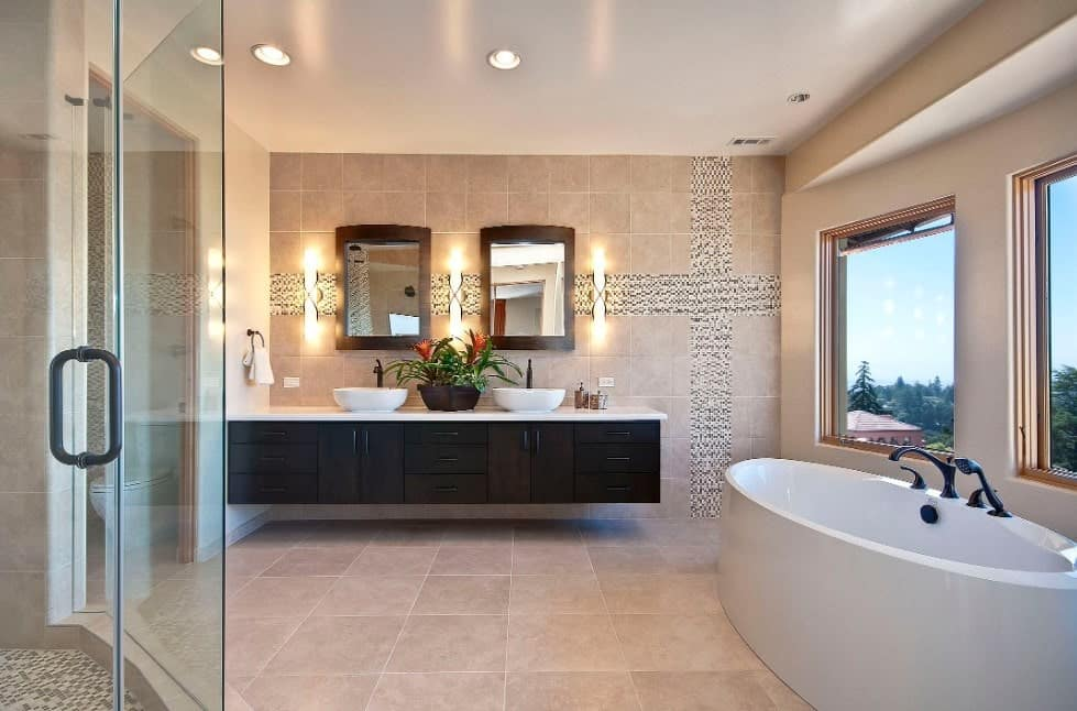 Spacious primary bathroom featuring tiles walls and flooring, along with a walk-in shower room, a floating vanity with two vessel sinks and a freestanding tub near the windows.