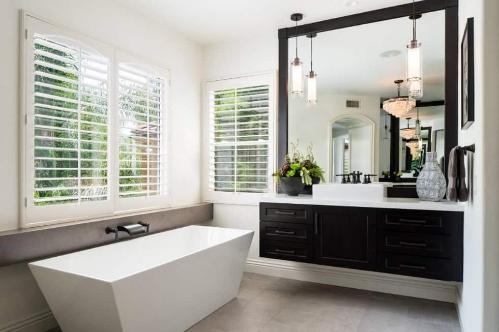 Primary bathroom featuring a white freestanding tub set on the gray tiles flooring and an espresso-finished floating vanity with a vessel sink.