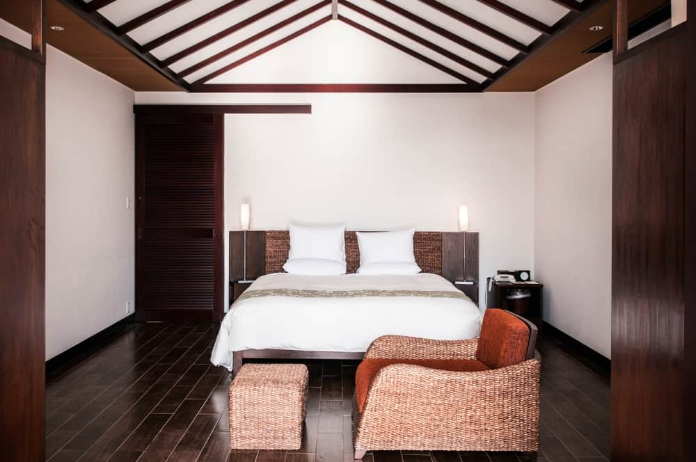 Master bedroom featuring an attractive bed and a chair with an ottoman, set on the hardwood flooring and is surrounded by white walls and a ceiling with exposed beams.