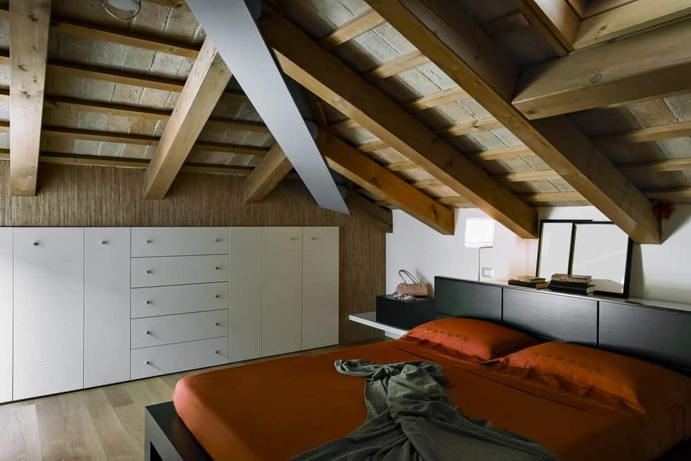 Master bedroom featuring a modish bed setup under the wooden ceiling with exposed beams.