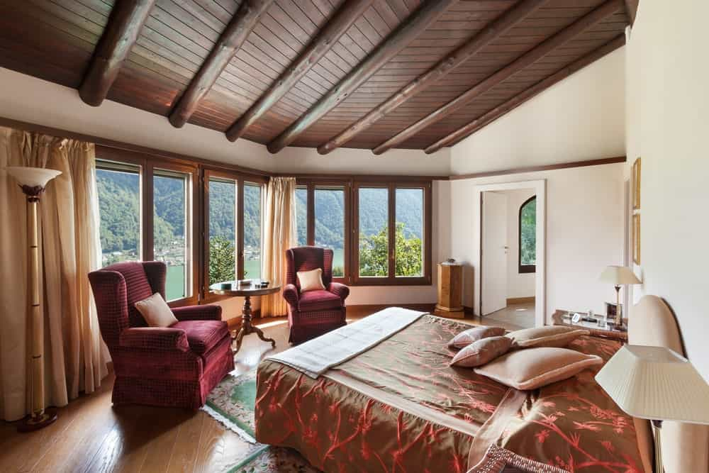 This master bedroom offers a classy bed with two red velvet chairs along with a coffee table. The room offers multiple glass windows overlooking the peaceful surroundings.