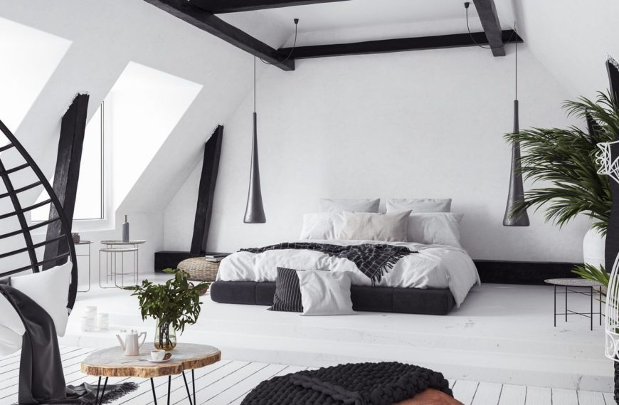 White master bedroom with a black accent for a more stylish look. It features a large cozy bed and other modish furniture, along with stylish pendant lights hanging from the ceiling with exposed beams.