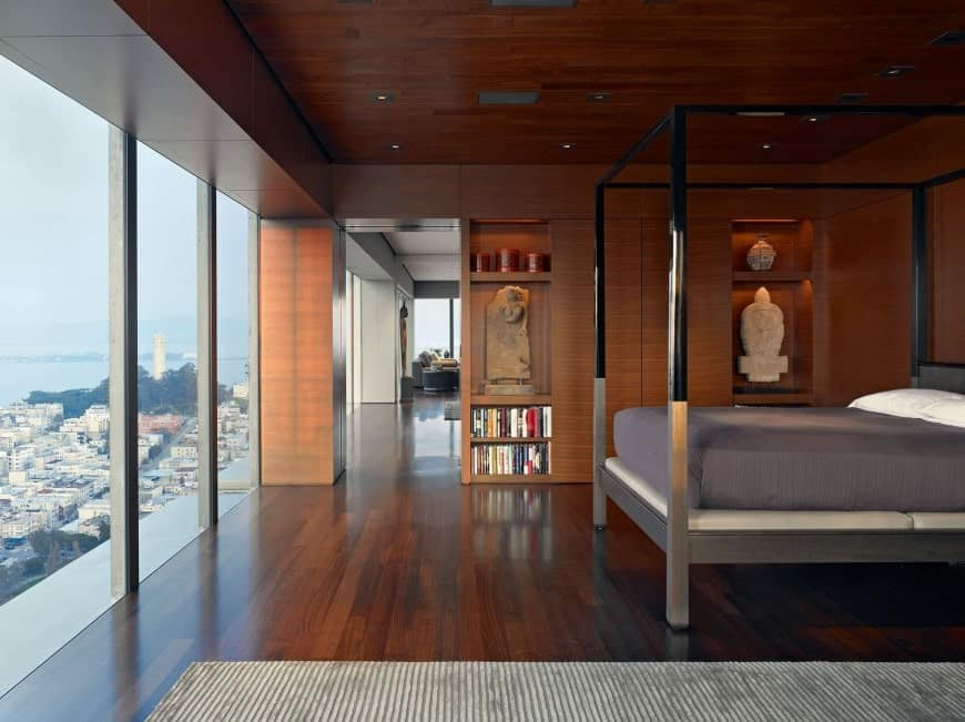 Primary bedroom featuring elegant wooden walls, ceiling and floors, along with glass windows overlooking the stunning outdoor view.