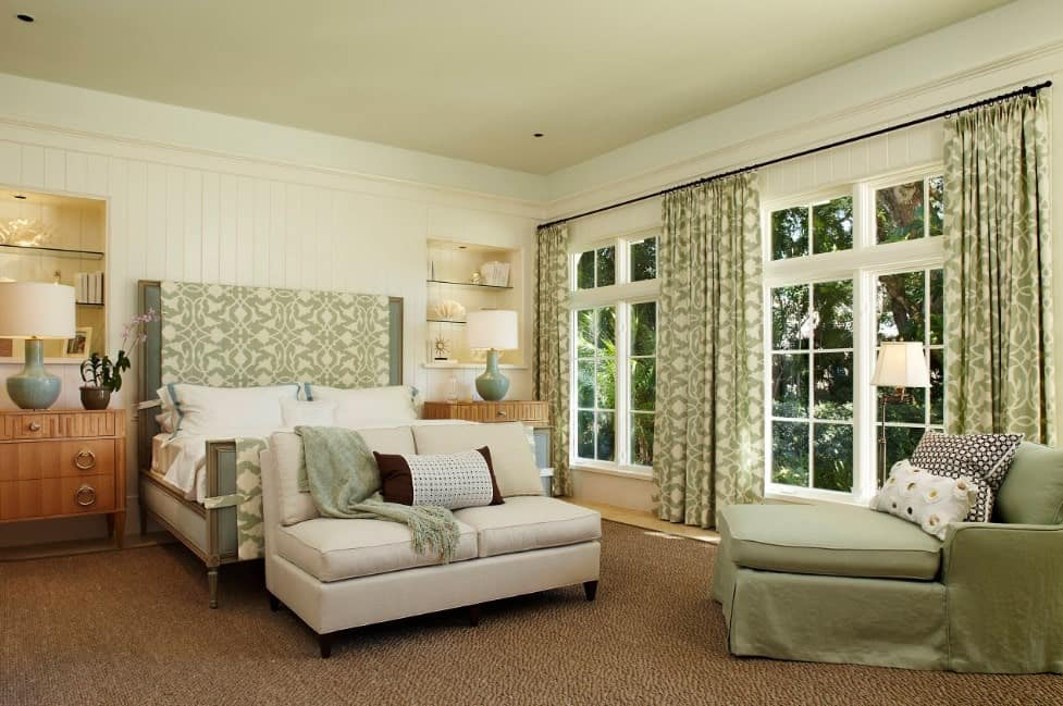 Primary bedroom featuring a green accent and carpet flooring. The bed looks so comfy together with the seats.