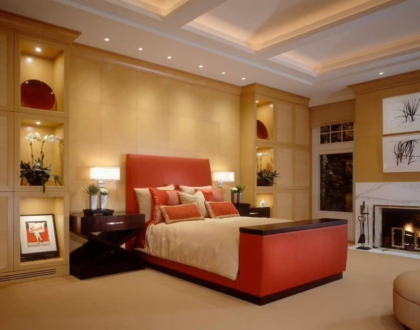 Luxurious primary bedroom with a stunning red bed with stylish side tables set on the carpet flooring. The ceiling looks absolutely attractive as well.