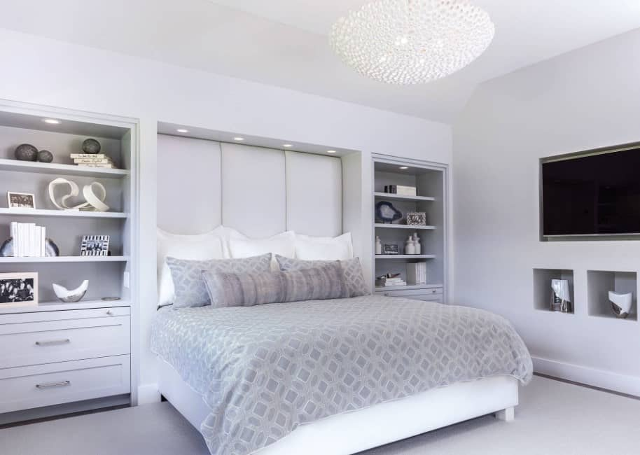 Master bedroom covered with white walls, floors and ceiling. It also features a ceiling lighting that is so bright.