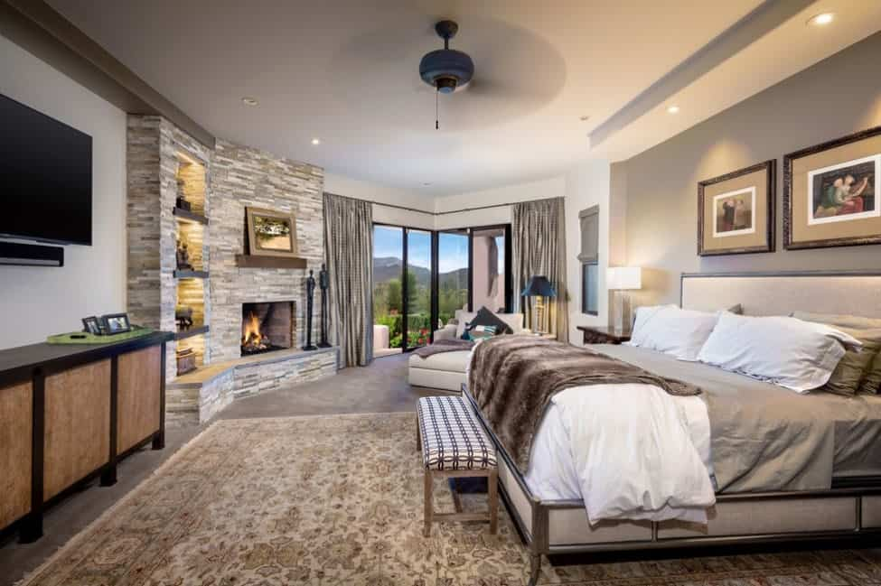 Large master bedroom featuring gray carpet flooring topped by a large rug, an extra large bed, a TV on the wall, a fireplace and a stunning view that can be overlooked through the glass windows.