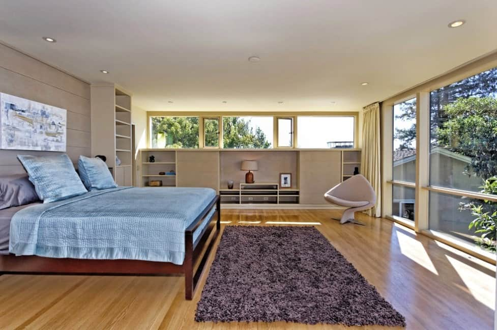 Primary bedroom featuring hardwood flooring and a regular ceiling, along with glass windows. There's a charming chair near the window.