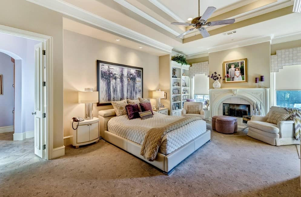 Master bedroom featuring carpet flooring and a stunning ceiling. The room offers a cozy bed and a sitting area near the fireplace.