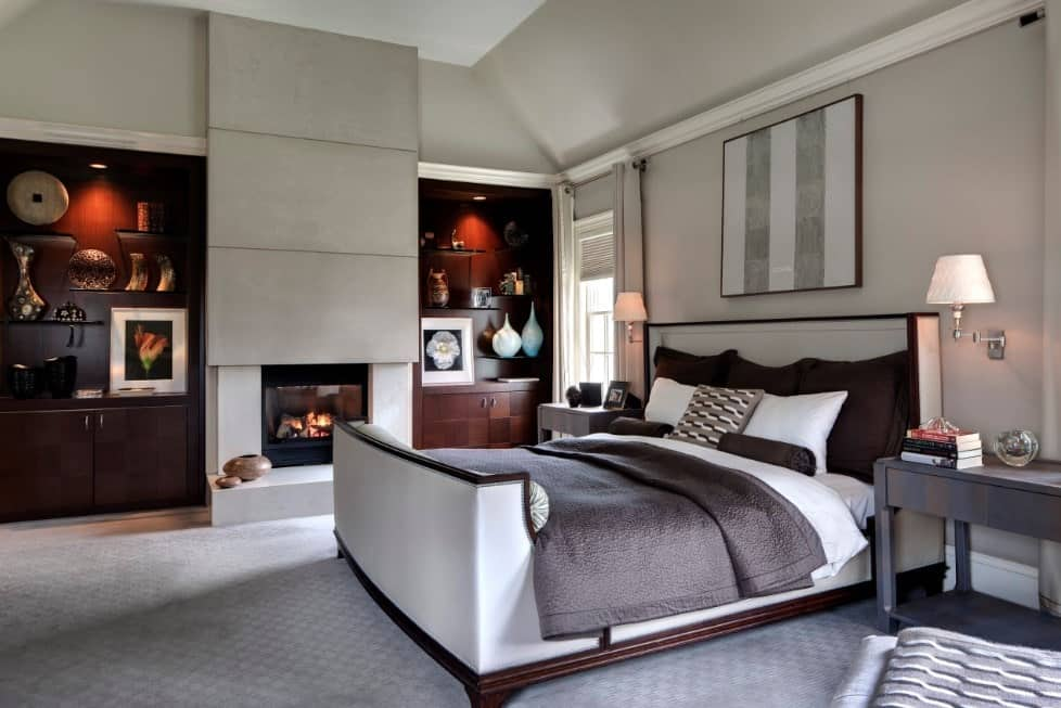 Primary bedroom featuring elegant shelving situated on both sides of the fireplace. The room has a cozy bed set on the carpet flooring.