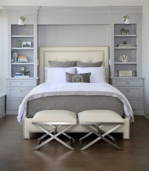 A close up look at this master bedroom's cozy bed with built-in shelves on both sides.