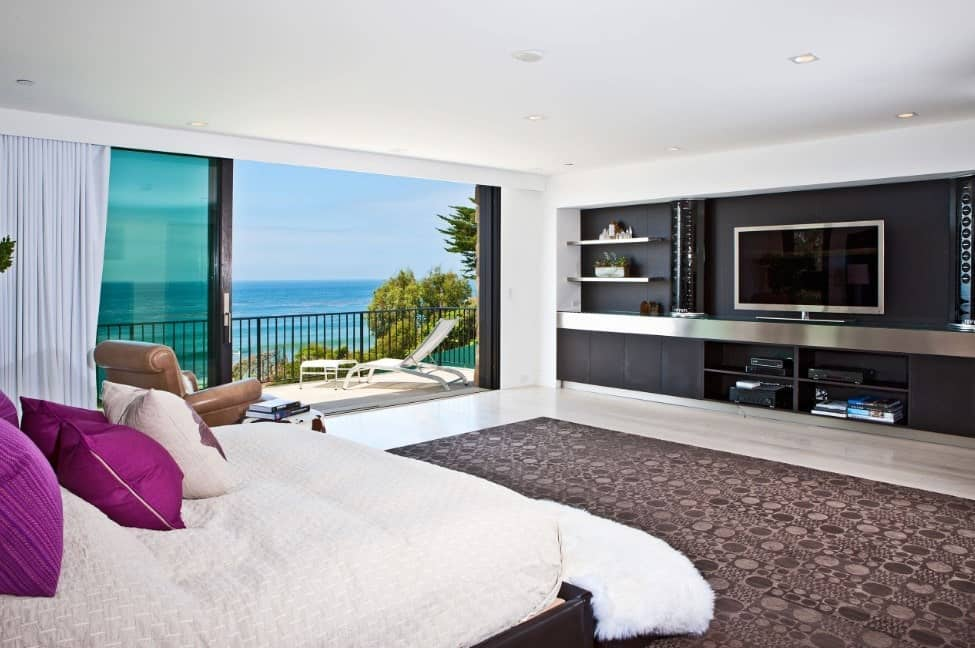 Spacious master bedroom featuring a modern TV stand with built-in shelving. The room offers a doorway leading to the private balcony overlooking the magnificent ocean view.