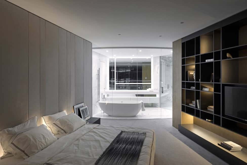 Contemporary primary bedroom with large shelving with a widescreen TV and a comfy bed set on the carpet flooring. The room also offers its own primary bathroom with a freestanding tub and a walk-in shower with marble tiles floors.