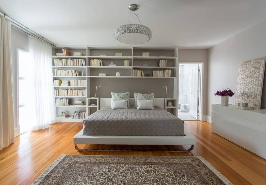 A master bedroom with gray shelving and walls, along with a white ceiling lighted by a charming ceiling lighting.