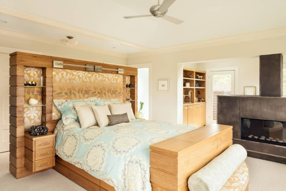 Primary bedroom with a stunning rustic bed frame and shelving, along with a fireplace on the side. The room boasts carpet flooring and a tray ceiling.